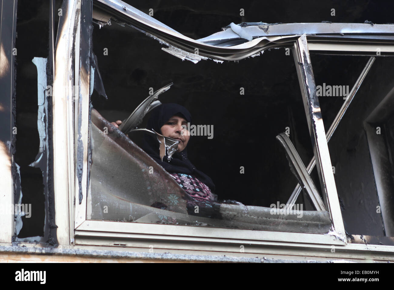 Ramallah, Ramallah. 23rd Nov, 2014. A Palestinian woman looks from a window of her relative's house which was - Stock Image