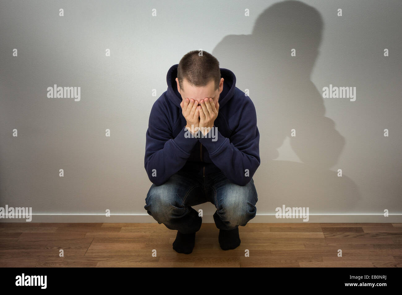 Man crouched and holding his face. Concept photo of anxienty, solitude and sorrow. - Stock Image