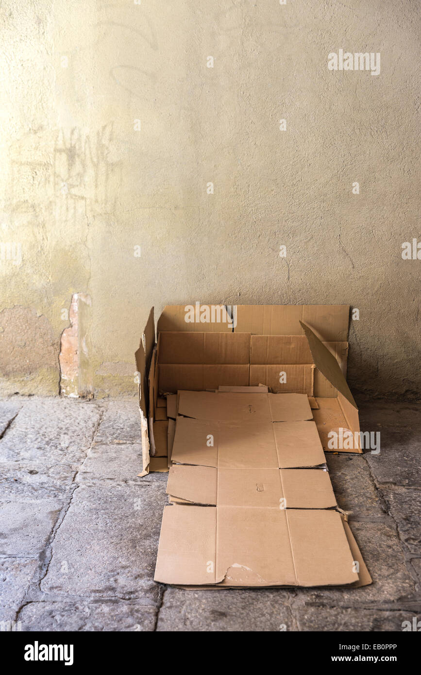 Bed made of cartons of a homeless man on a street covered with old stone floor of the old town of Barcelona. - Stock Image
