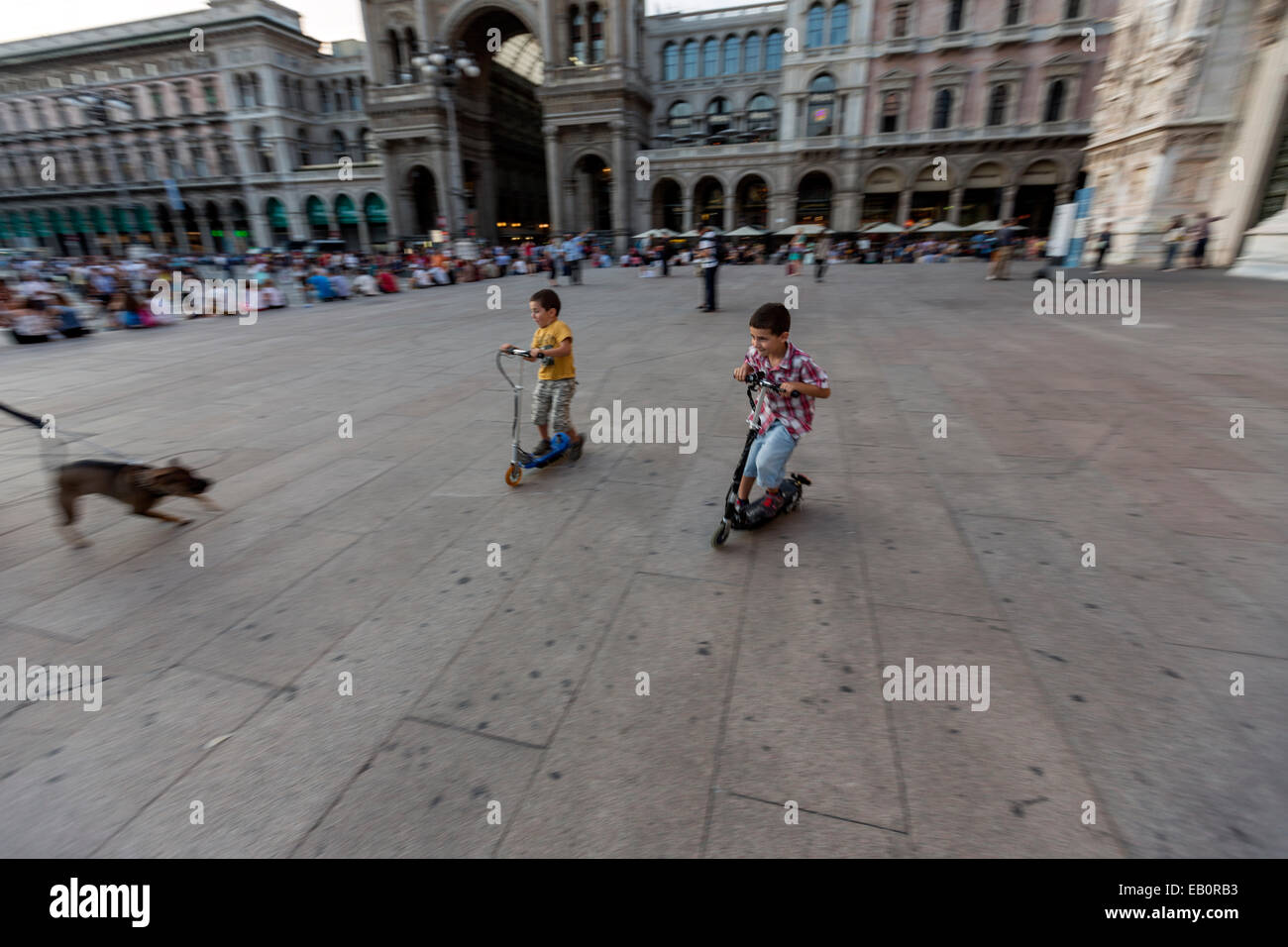 Boys playing with scooters being frightening with a dog in the  Piazza del Duomo  Milan - Stock Image