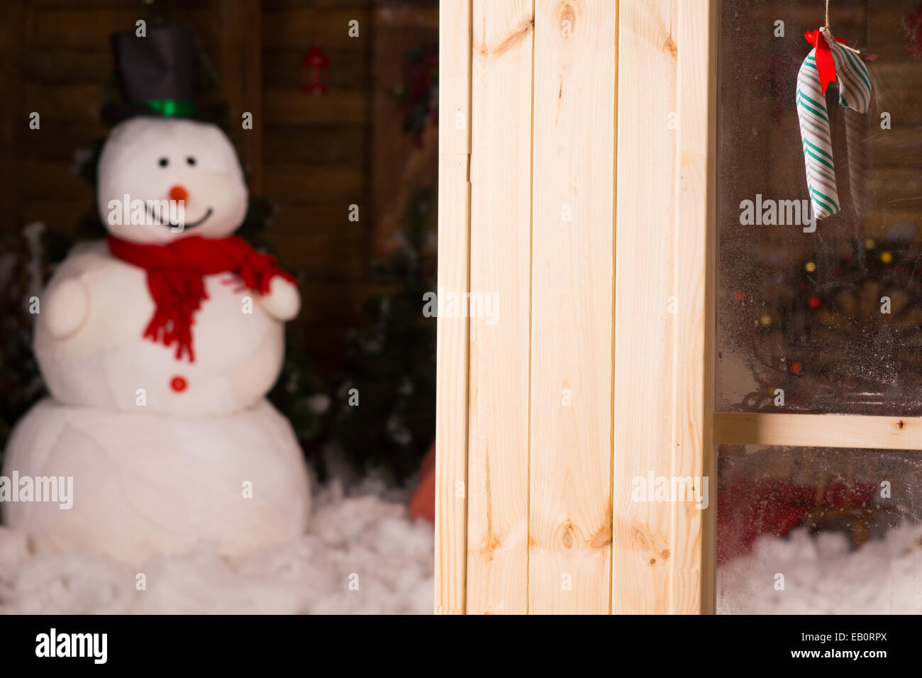 Macro Colored Small Candy Cane Hanging on Glass Window with Snowman and Christmas Decors Inside the House. - Stock Image