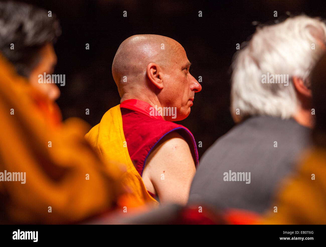 Buddhist monk Nicholas Vreeland listens as the Dalai Lama speaks to Buddhist monks and a public audience in New - Stock Image