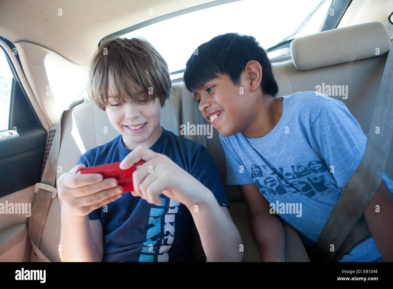 Two Ten Year Old Boys Watch A Video On A Phone, Back Seat