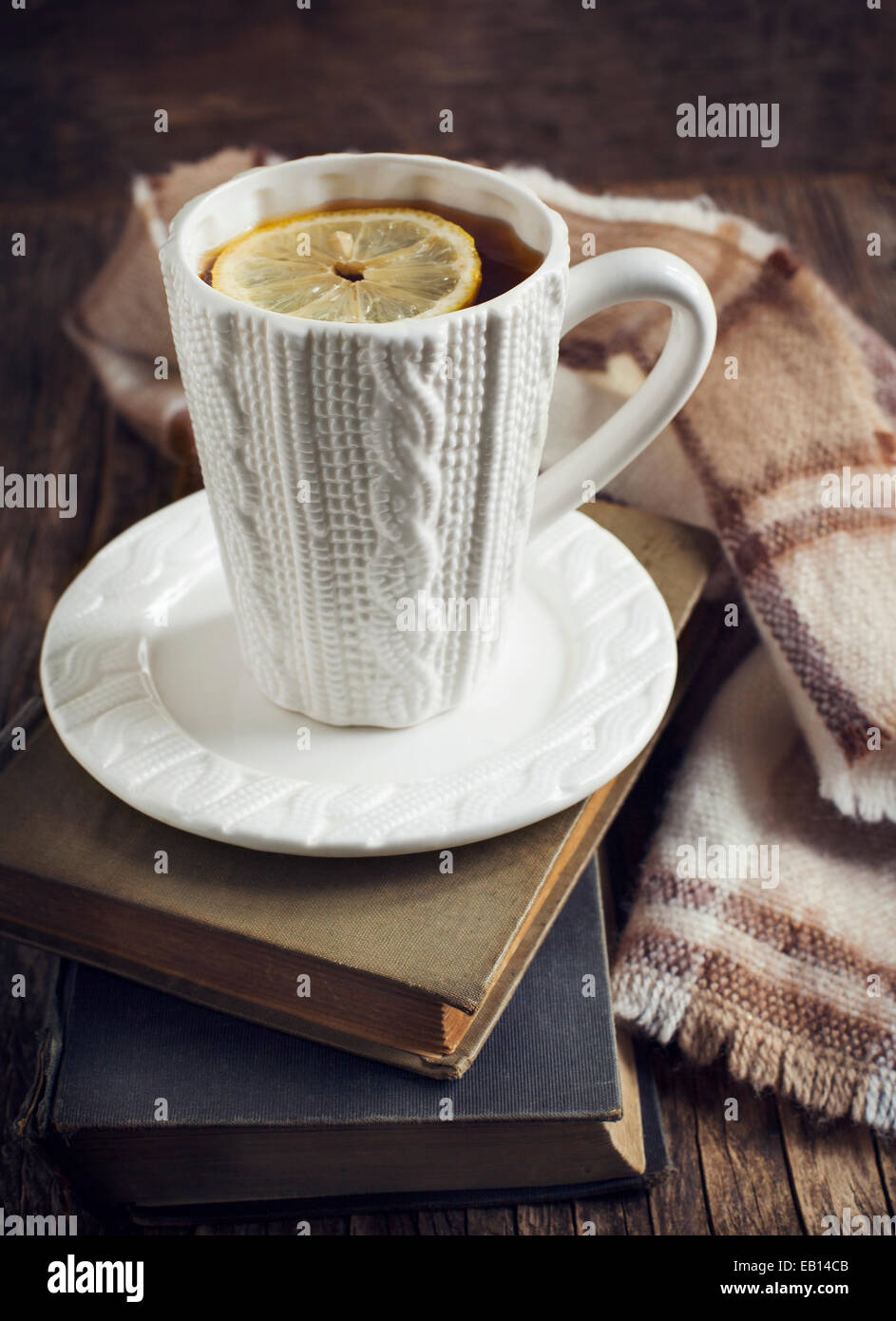 Cup of hot tea with lemon, book and scarf on wooden table. - Stock Image