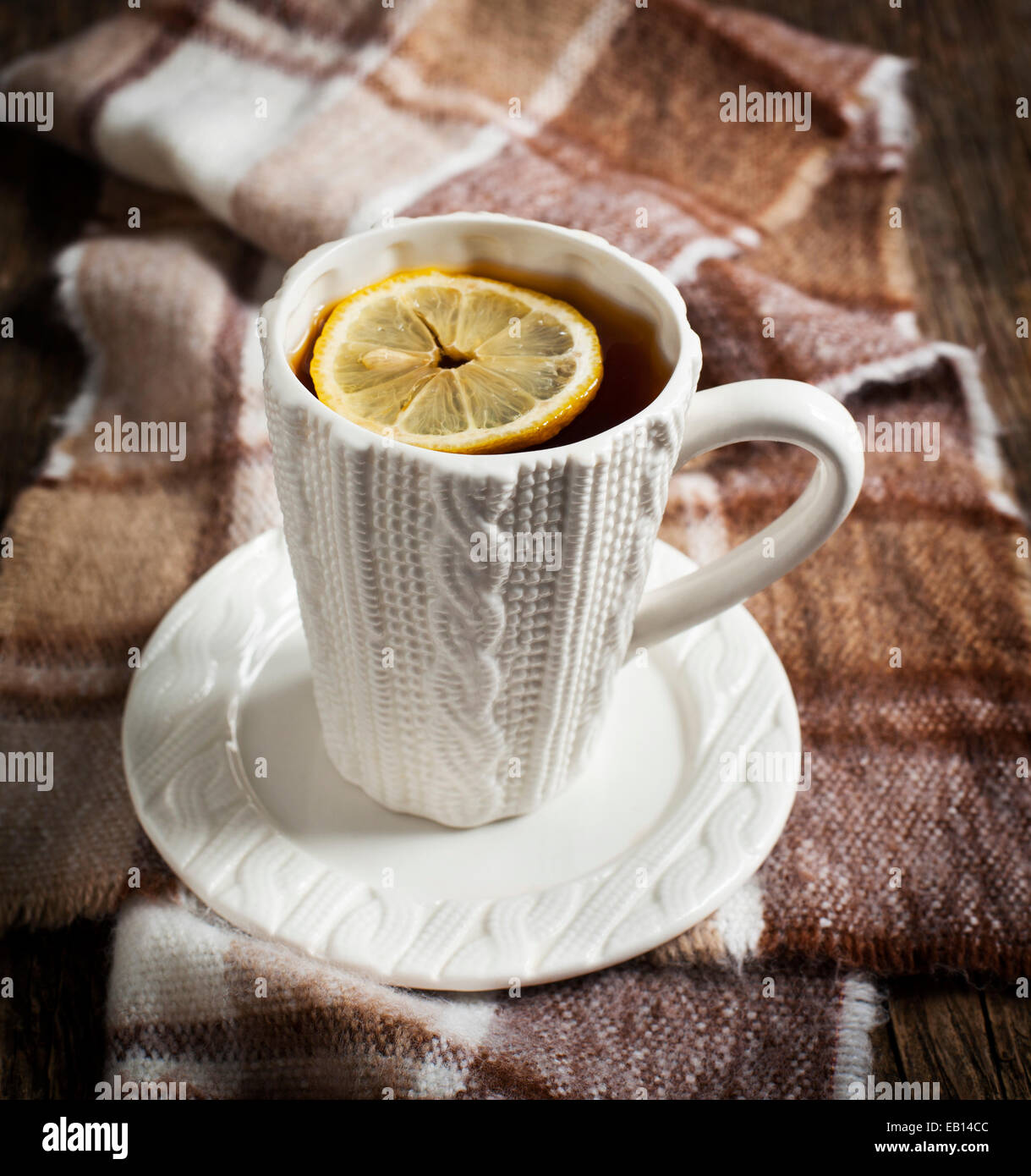 Cup of hot tea with lemon and scarf on wooden table. - Stock Image