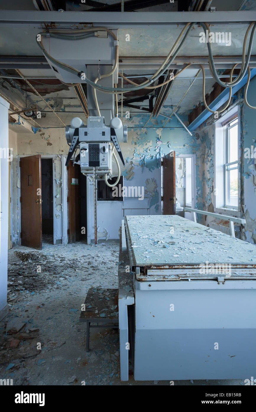 A Radiology room table and an X-ray generator in an abandoned hospital. Ontario, Canada. - Stock Image