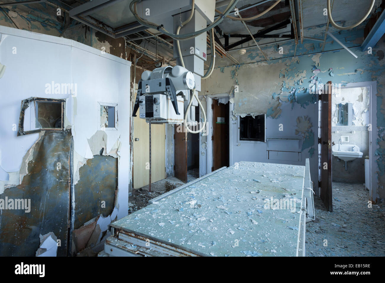 A Radiology room table, an X-ray generator and an exposed lead wall in an abandoned hospital. Ontario, Canada. - Stock Image