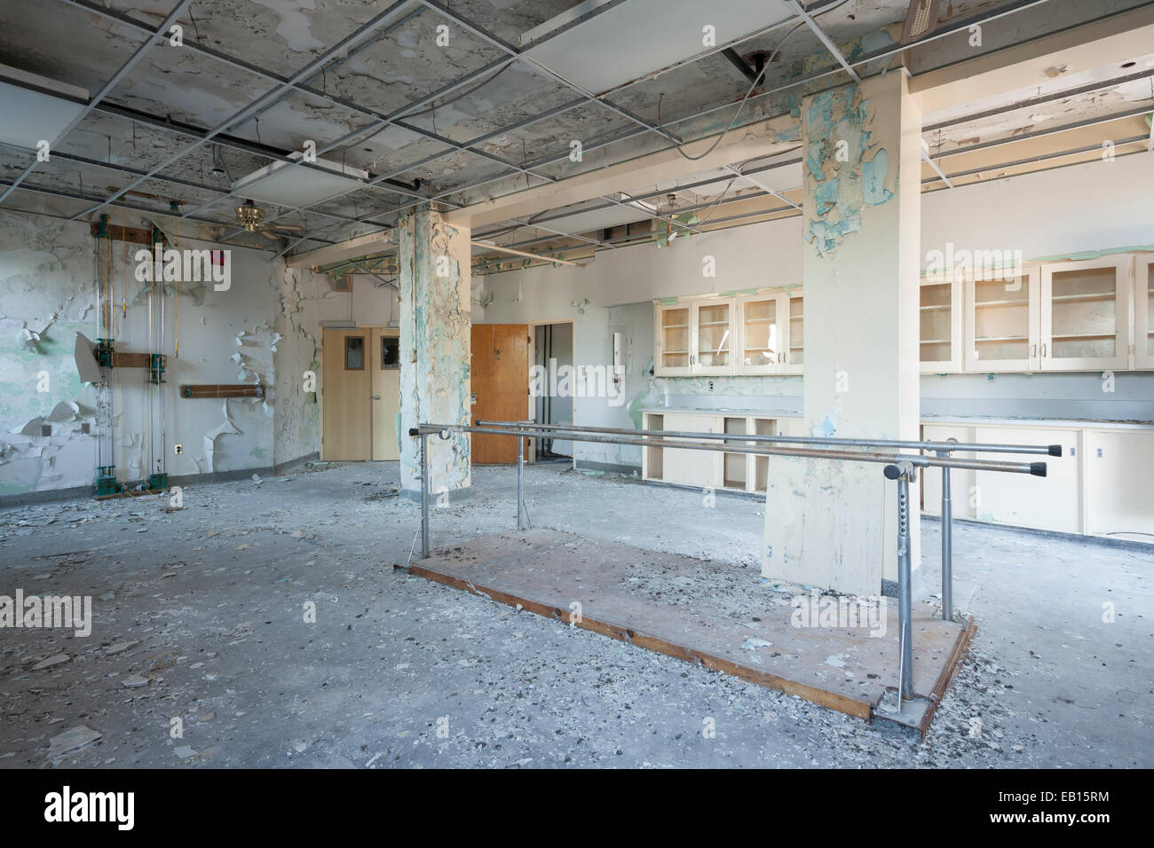 Parallel bars and chest pulley weight system in the Physical Therapy room of an abandoned hospital. Ontario, Canada. - Stock Image
