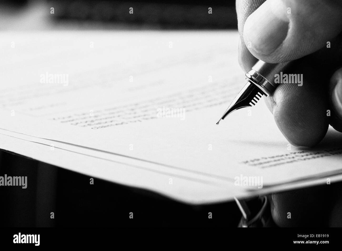 A hand holding a fountain pen and about to sign a letter. Styling and small amount of grain applied. - Stock Image