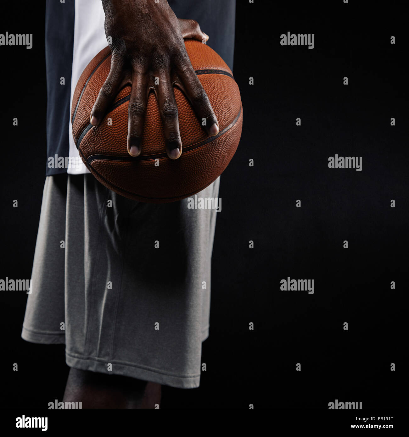 Cropped image of a young man holding basketball against black background. Mid section image of African basketball - Stock Image