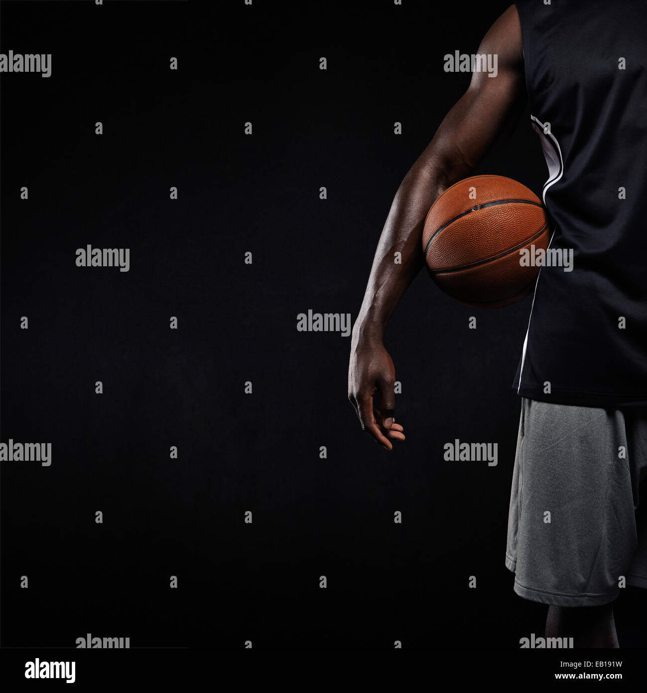 Cropped image of black basketball player standing with a basket ball. Man in sportswear holding basketball with - Stock Image