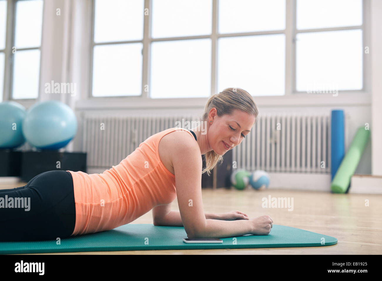 Fitness woman lying on exercise mat looking at her mobile phone. Caucasian woman using smart phone while exercising - Stock Image