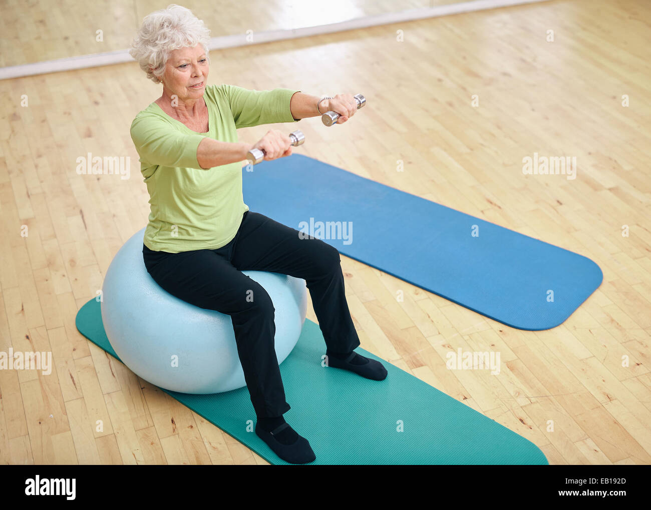 Senior female sitting on a fitness ball and lifting dumbbells. Old woman exercising with weights at gym. - Stock Image