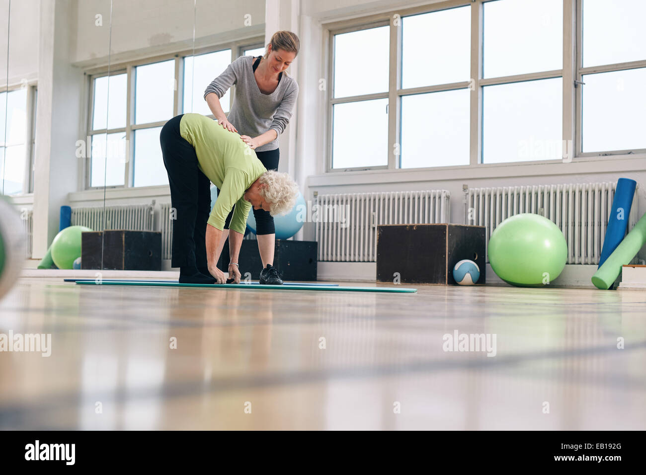 Senior woman bending forward and touching her toes being helped by personal trainer at health club. Elder woman - Stock Image