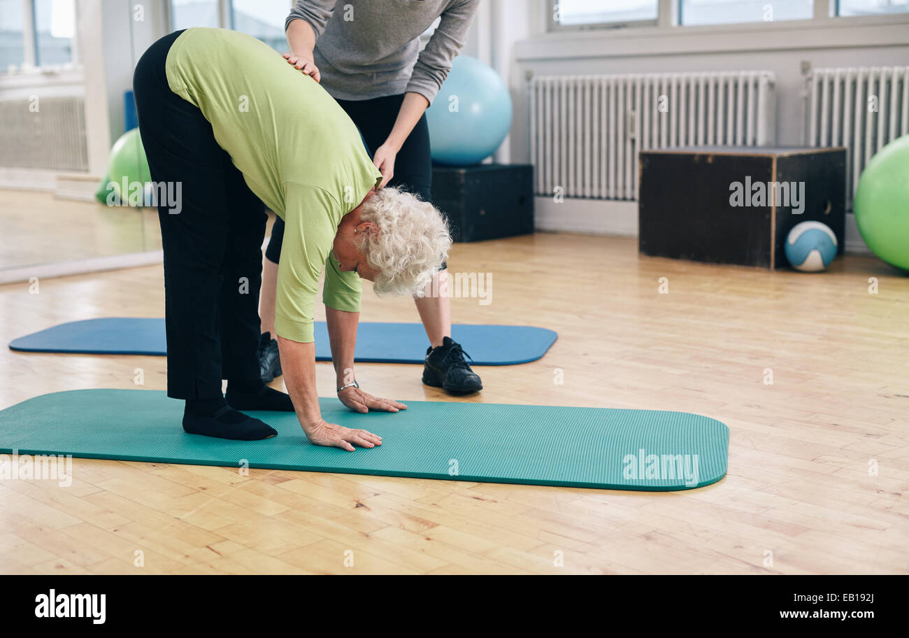 Senior woman bending forward and touching her toes being helped by gym instructor. Elder woman doing back exercise. - Stock Image