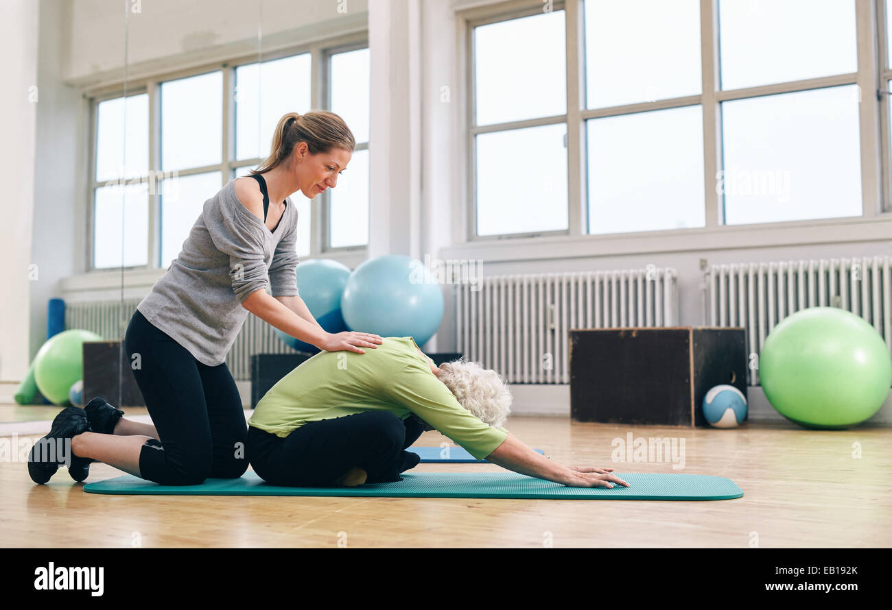 Female trainer helping senior woman to bend over. Old woman doing yoga on a exercise mat with physical therapist - Stock Image