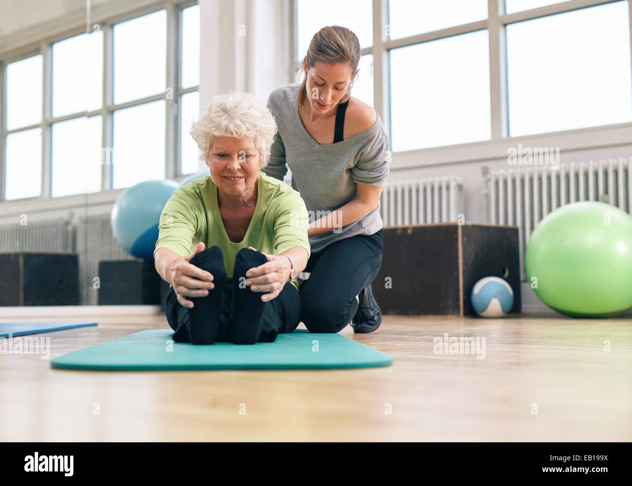 Elderly woman being helped by her instructor in the gym for exercising. Senior woman sitting on fitness mat bending - Stock Image