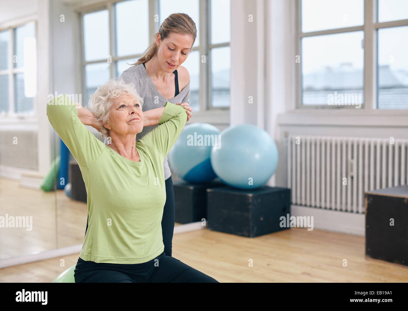 Senior women doing light pilates workout for back muscles with coach assistance. Trainer helping senior woman exercising - Stock Image