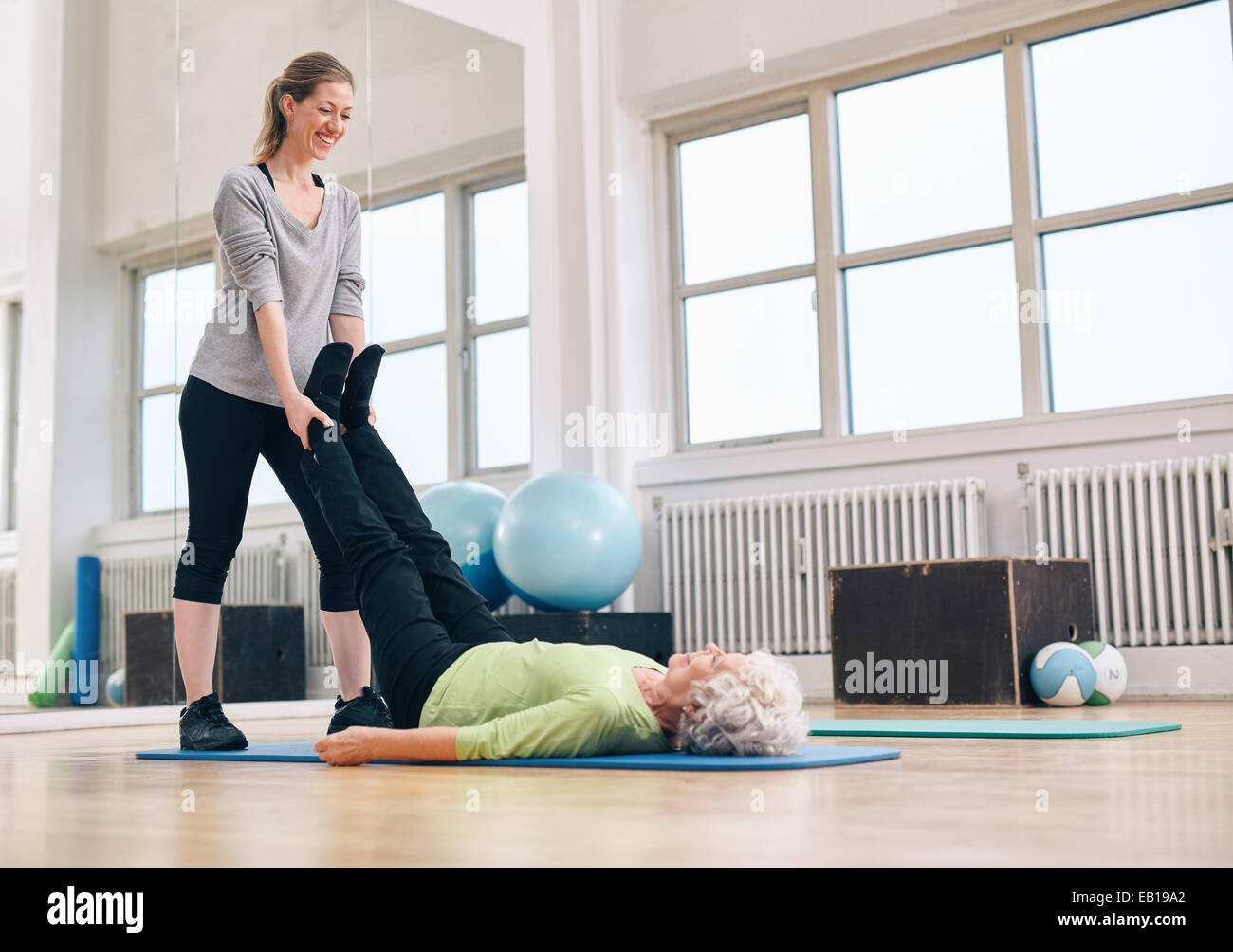 Personal trainer working with client on exercise mat at the gym. Instructor holding legs of senior woman exercising. - Stock Image