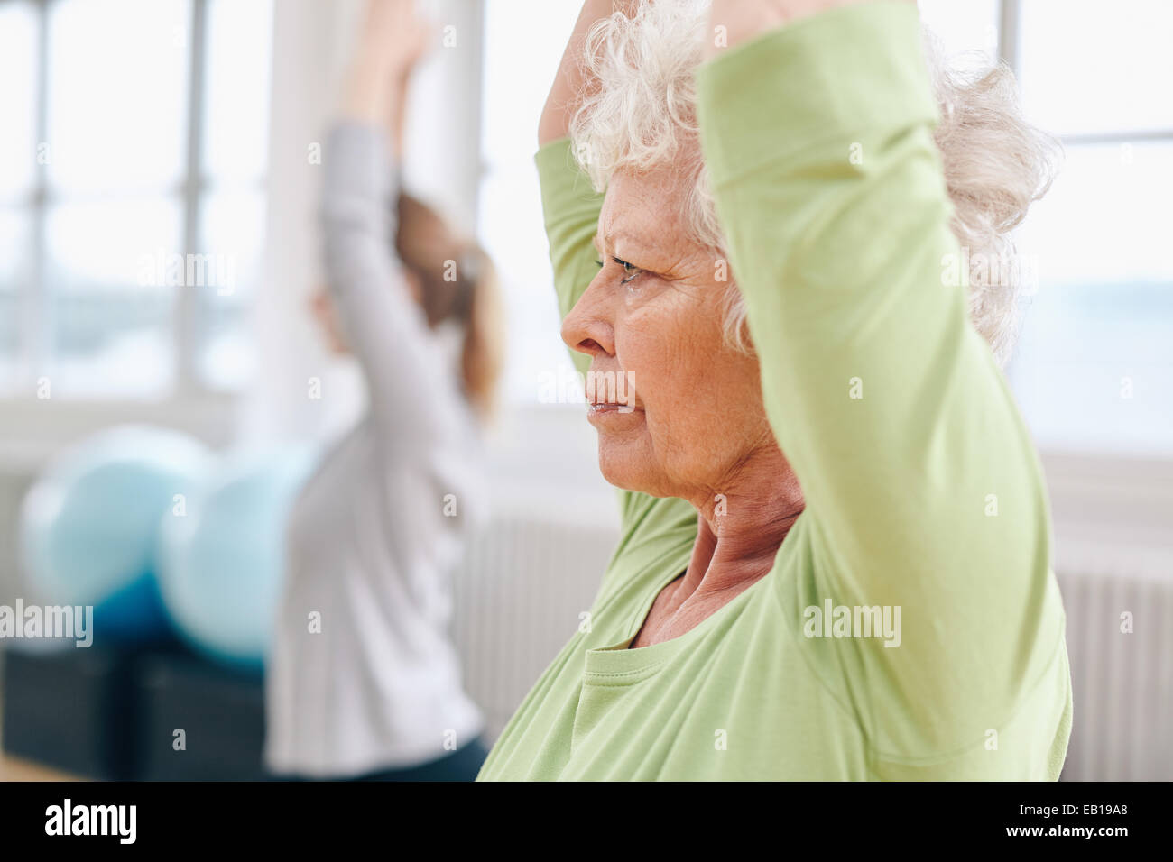 Close-up image of senior woman practicing yoga at gym. Active senior woman exercising at health club with female - Stock Image