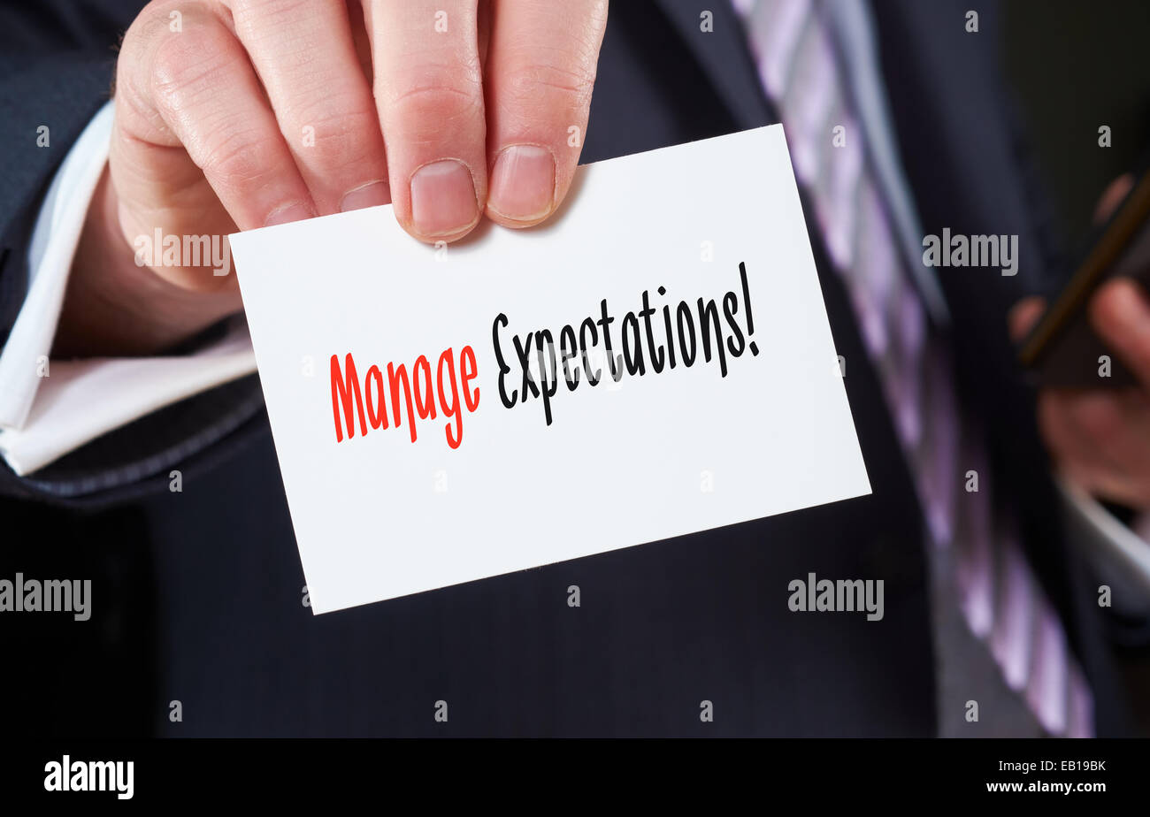 A businessman holding a business card with the words, Manage Expectations, written on it. - Stock Image