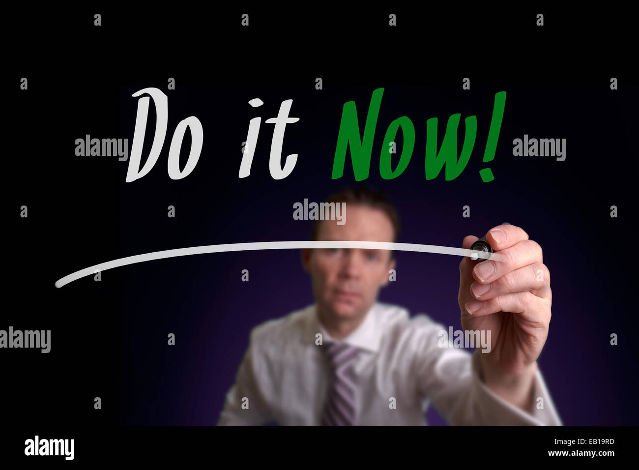A businessman writing Do it Now on a screen. Business Concept. - Stock Image