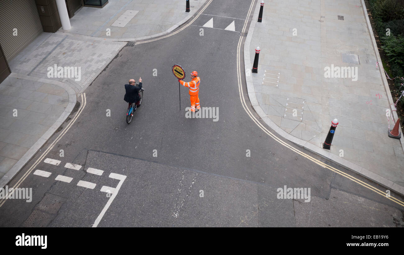 Asking directions from Banksman traffic marshall with fluorescent suit and helmet with stop works sign directing Stock Photo