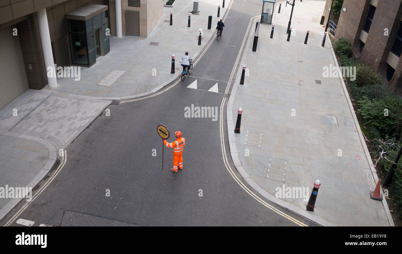 Banksman traffic marshall  with fluorescent suit and helmet with stop works sign directing Boris bikes in London - Stock Image
