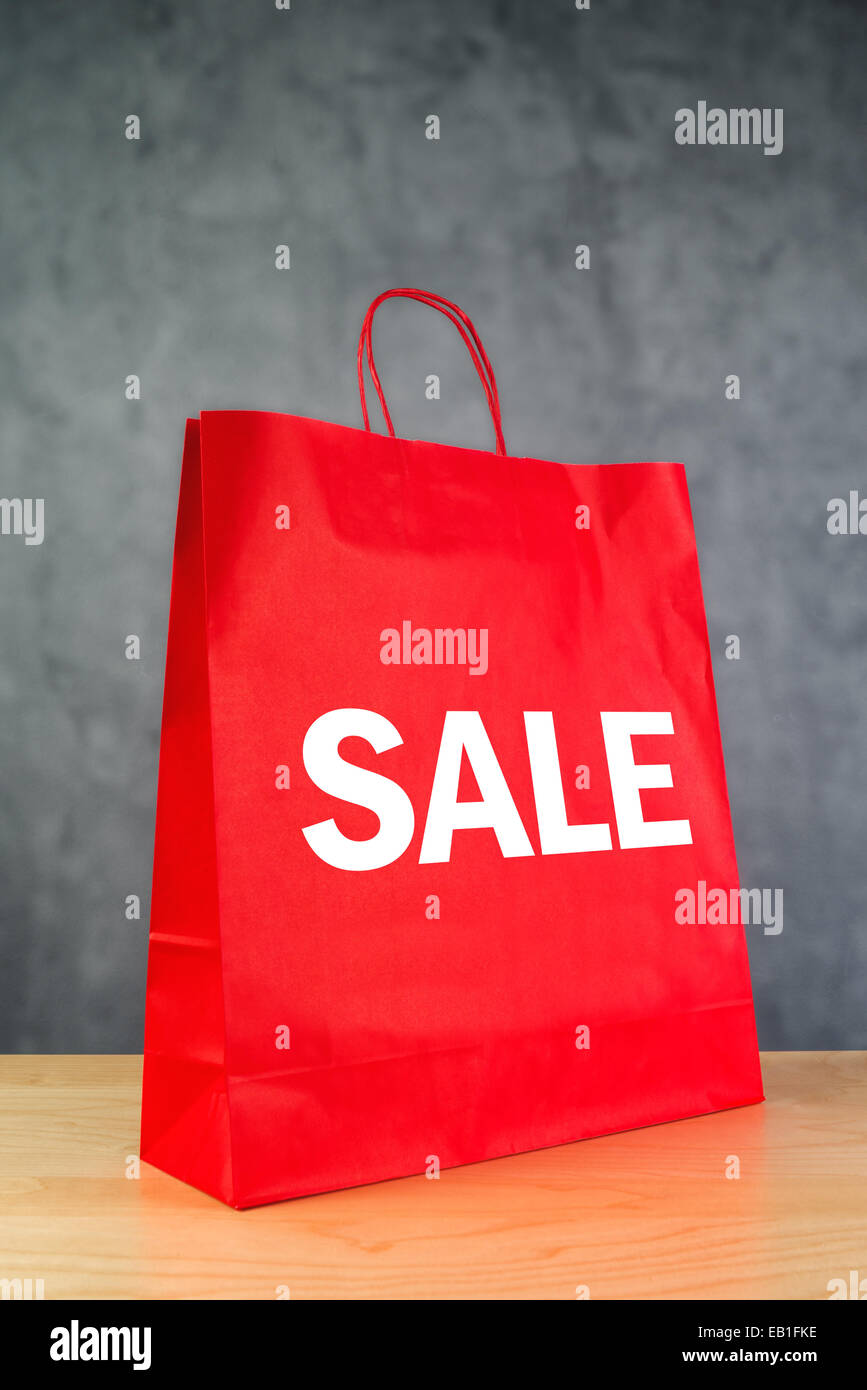 Clearance Sale Red Paper Shopping Bag on Wooden Retail Store Table. - Stock Image