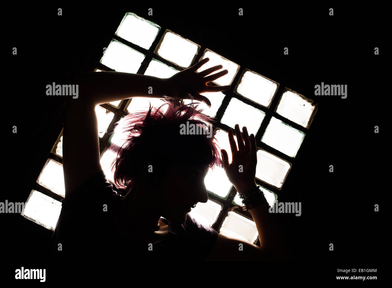 A young teenage girl woman trapped confined in a prison cell type location with light streaming through a barred - Stock Image