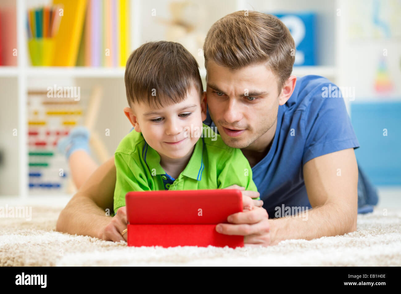 dad and son kid play with tablet computer indoors - Stock Image