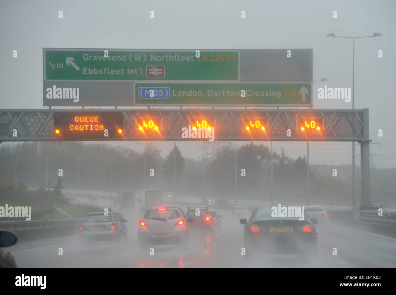 Speed limits and Queue warning signs light up during pouring rain over the M2 motorway in the UK - Stock Image