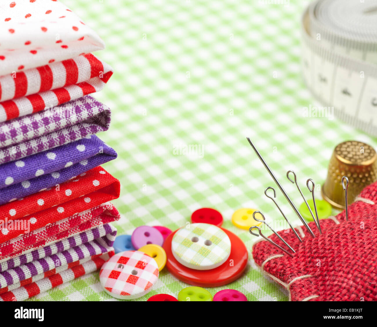 Sewing items: buttons, colorful fabrics, measuring tape, pin cushion, thimble - Stock Image