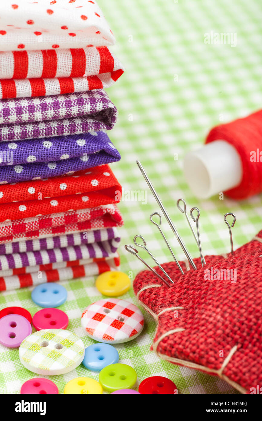 Sewing items: colorful fabrics, buttons, pin cushion, thimble, spool of thread - Stock Image