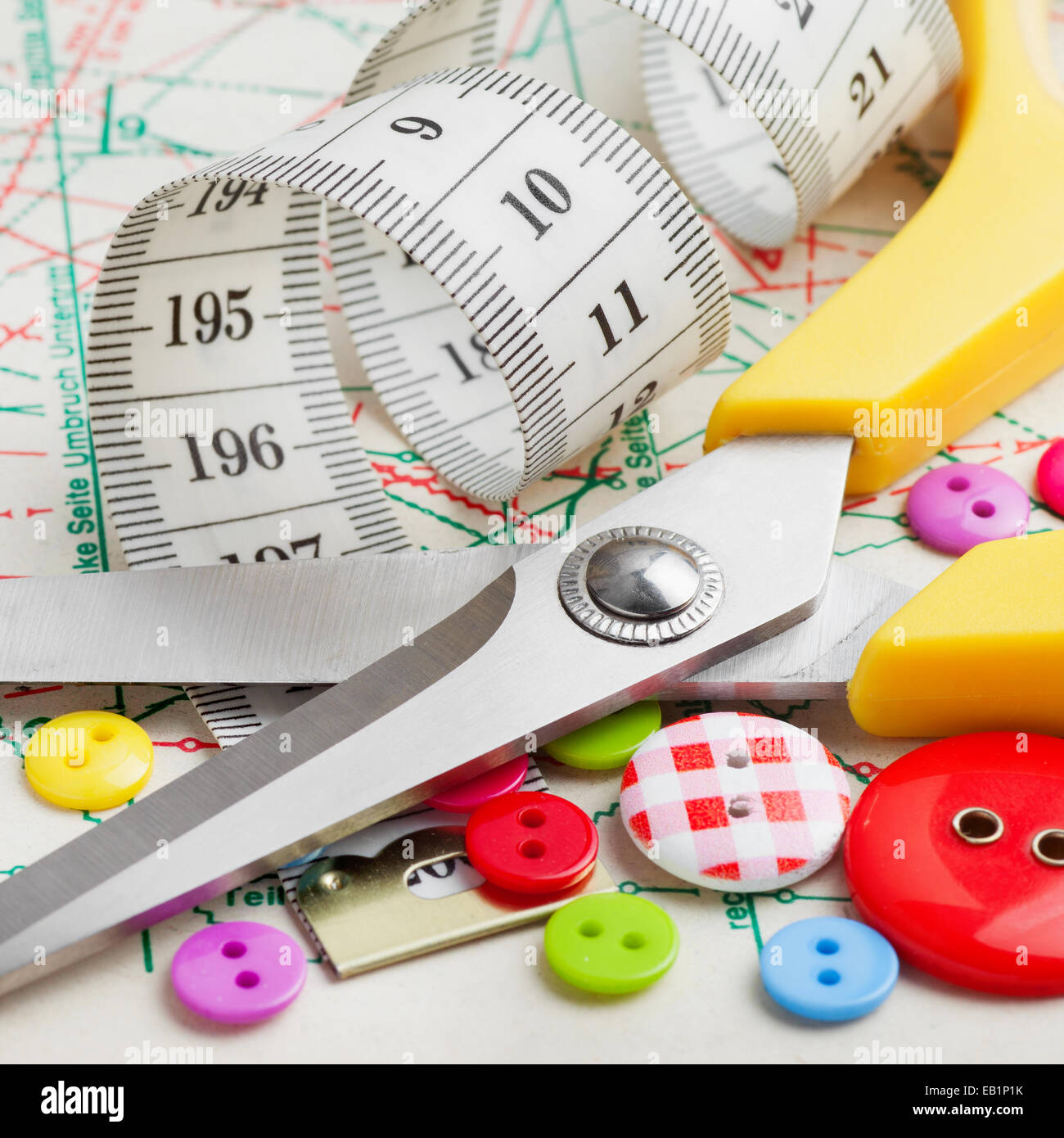 Sewing items: buttons, scissors, measuring tape  on sewing pattern - Stock Image