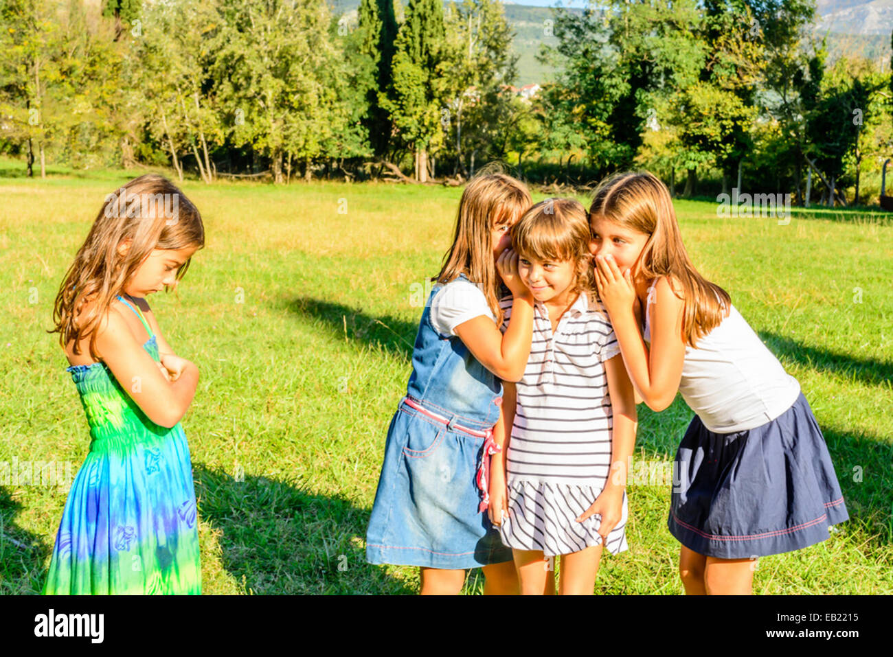 Four little girls  playing together and are whispering secrets - Stock Image