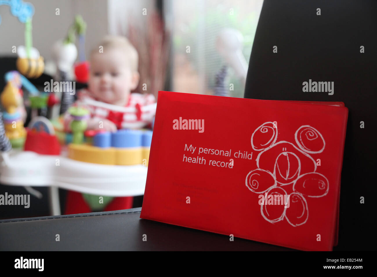 A red personal child health record book, issued to new children born in the UK and taken to each development appointment. - Stock Image