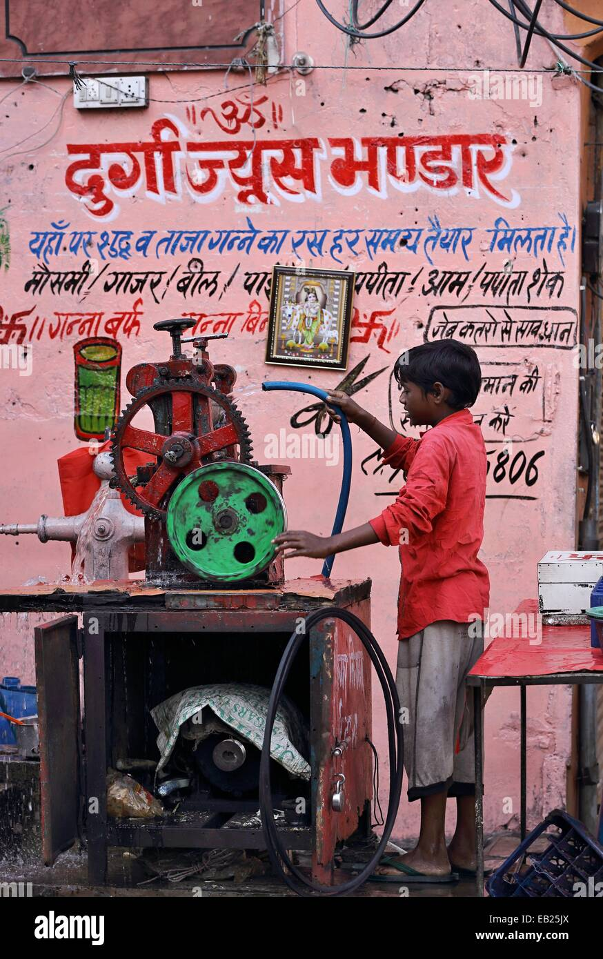 Young Indian boy cleaning a sugarcane juice machine India - Stock Image