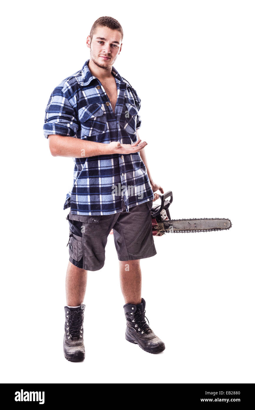 a young lumberjack wearing a checkered shirt holding a chainsaw and showing something isolated over white background Stock Photo