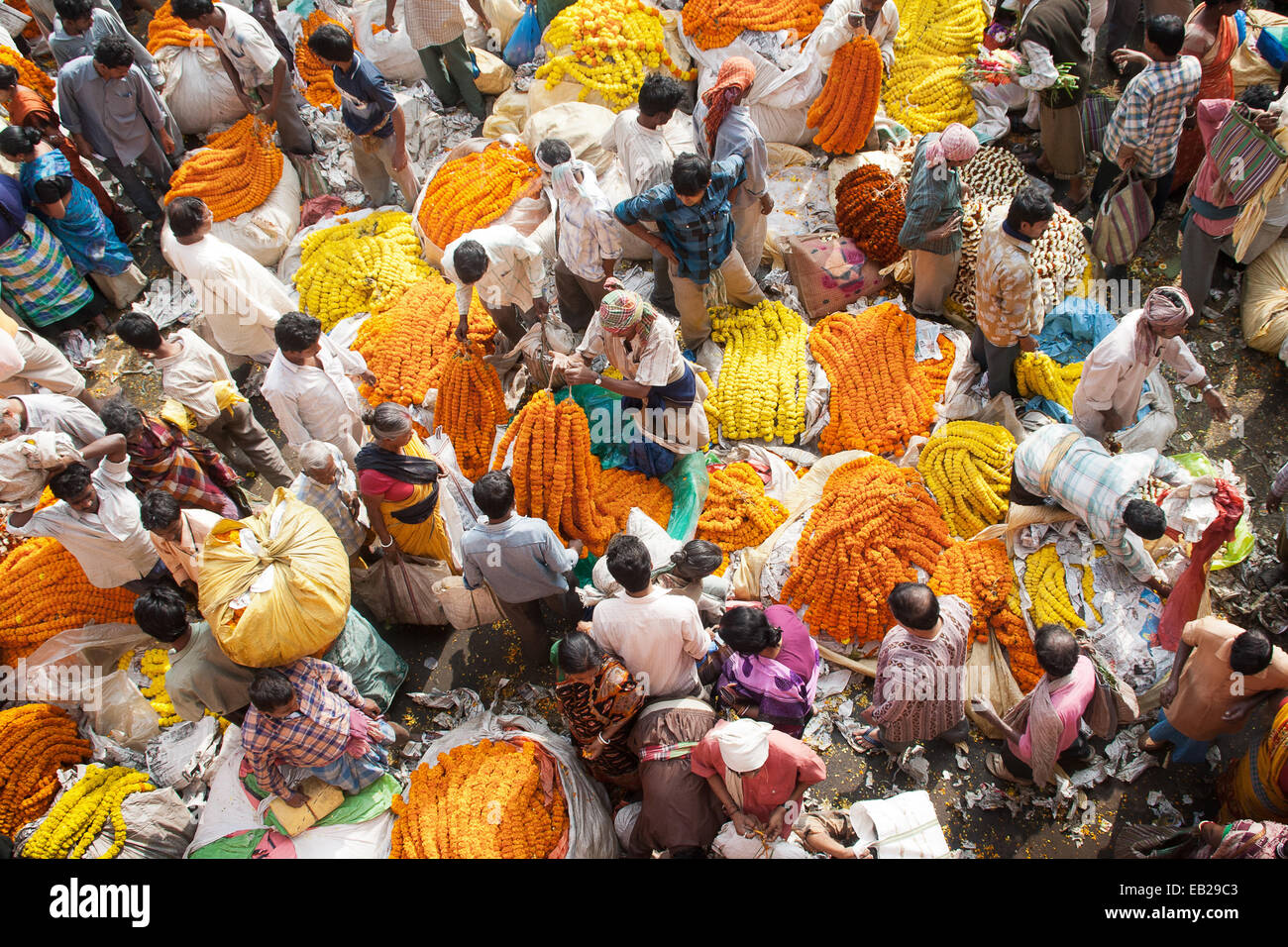 Aerial view of flower market bustling with activity and sack bags full of colorful flowers and garlands with sellers - Stock Image