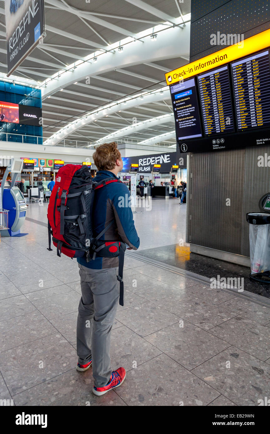Backpacker Looking At Departure Screens, Heathrow Airport, London, England - Stock Image