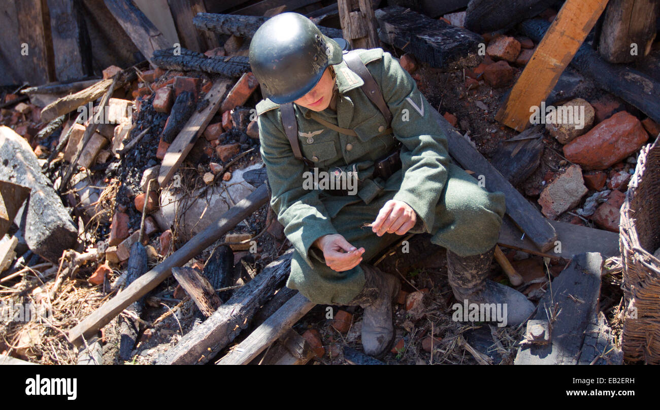 A supporting actor as German soldiers sits in front of a ruin during the filming of the German TV production of - Stock Image
