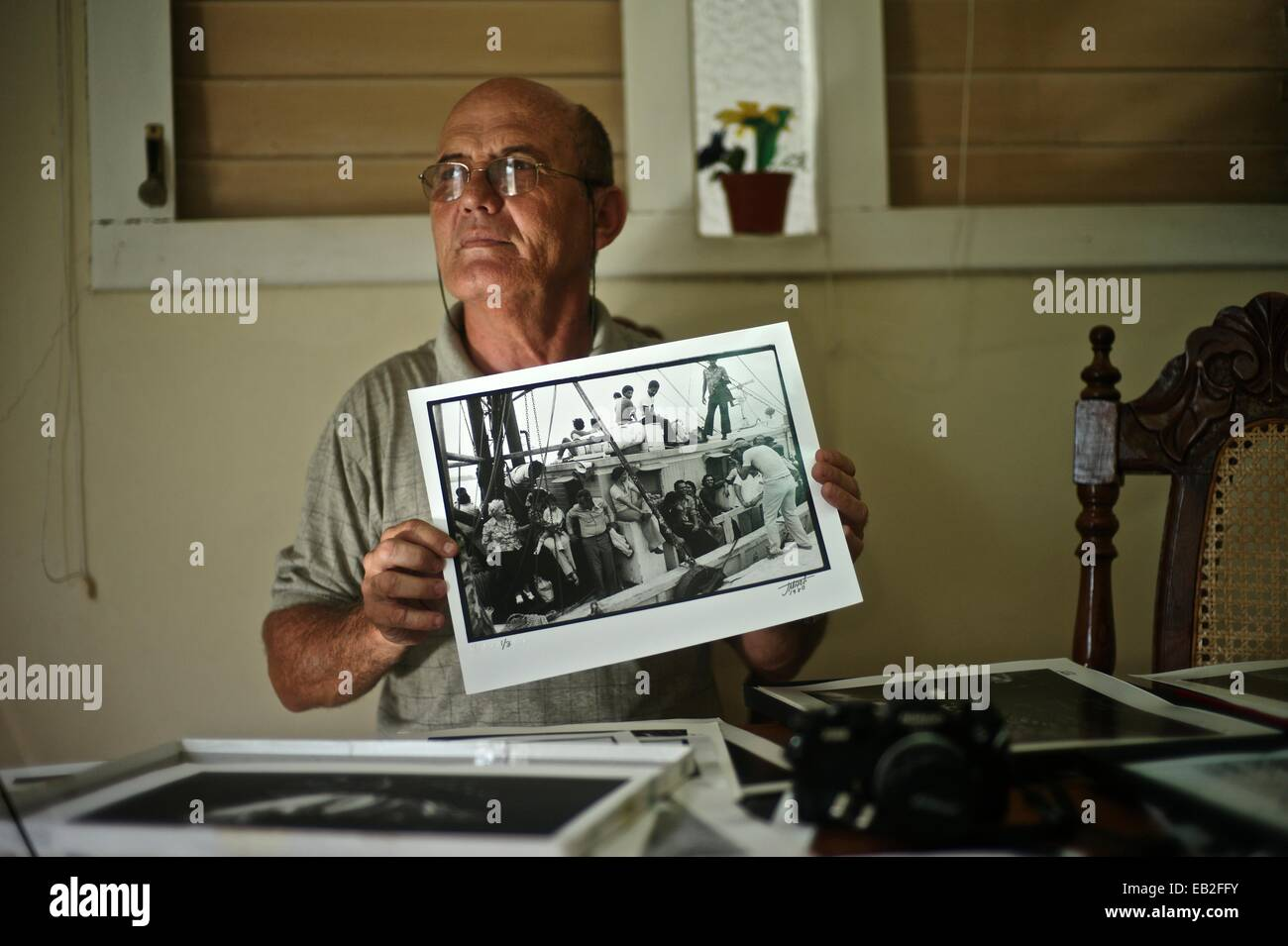 Cuban photographer Jose Marti, holding a photograph of the Mariel boatlift, at his home in Havana. Stock Photo
