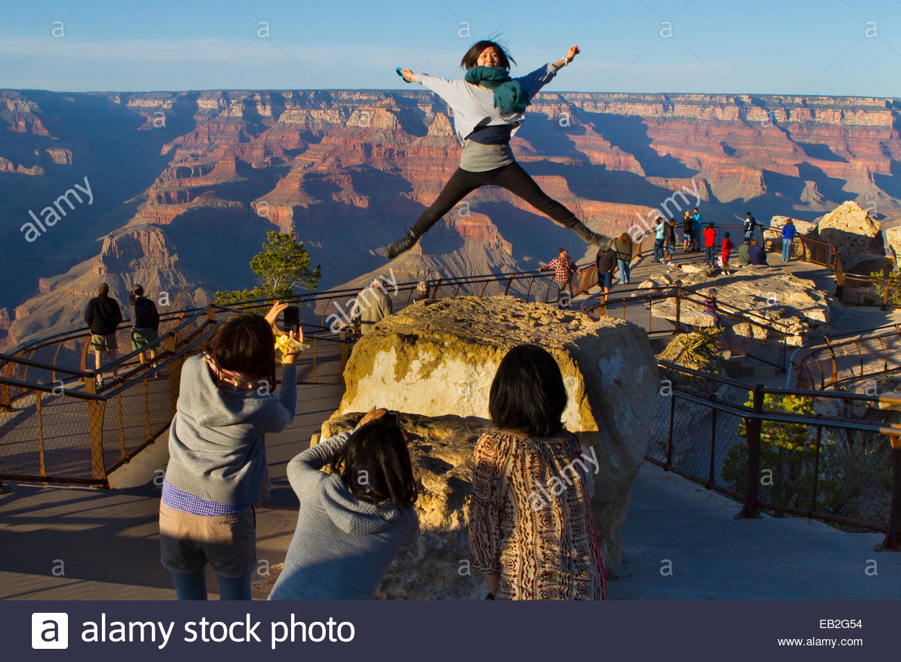 A young woman is photographed by her friends as she leaps above the Grand Canyon at Mather Point on the South Rim. - Stock Image