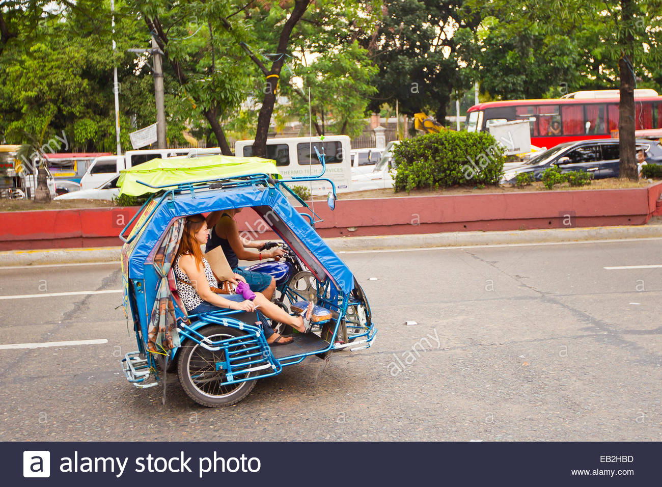 A family travels in downtown Manila in a tri-wheeled scooter. - Stock Image