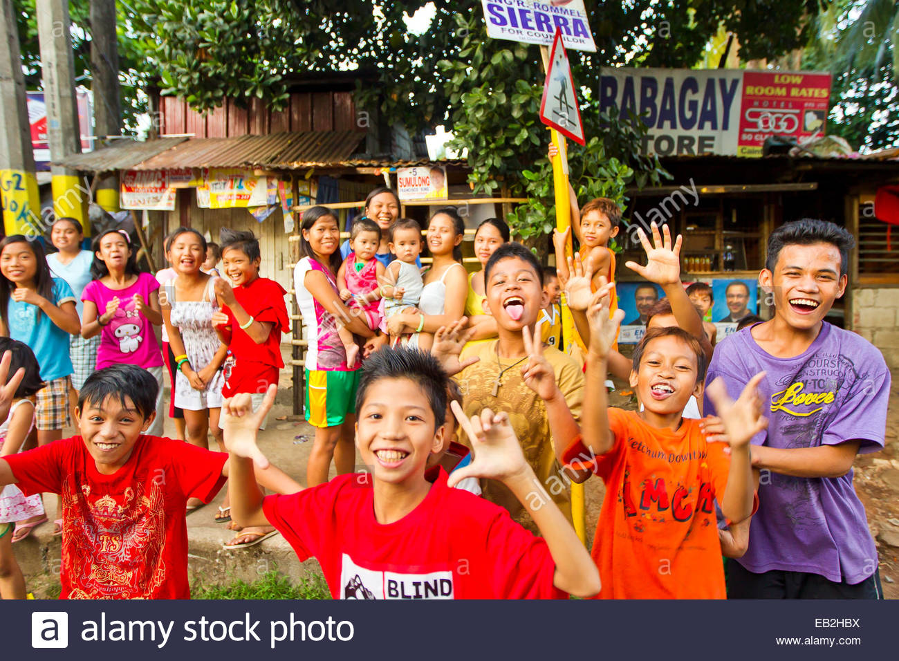 Kids line the streets of Manila as a parade for the upcoming political elections takes place. - Stock Image