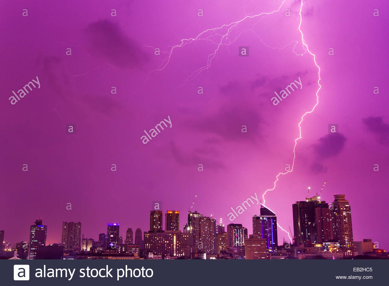 A intense thunderstorm with lightning over the skyline of Manila. - Stock Image