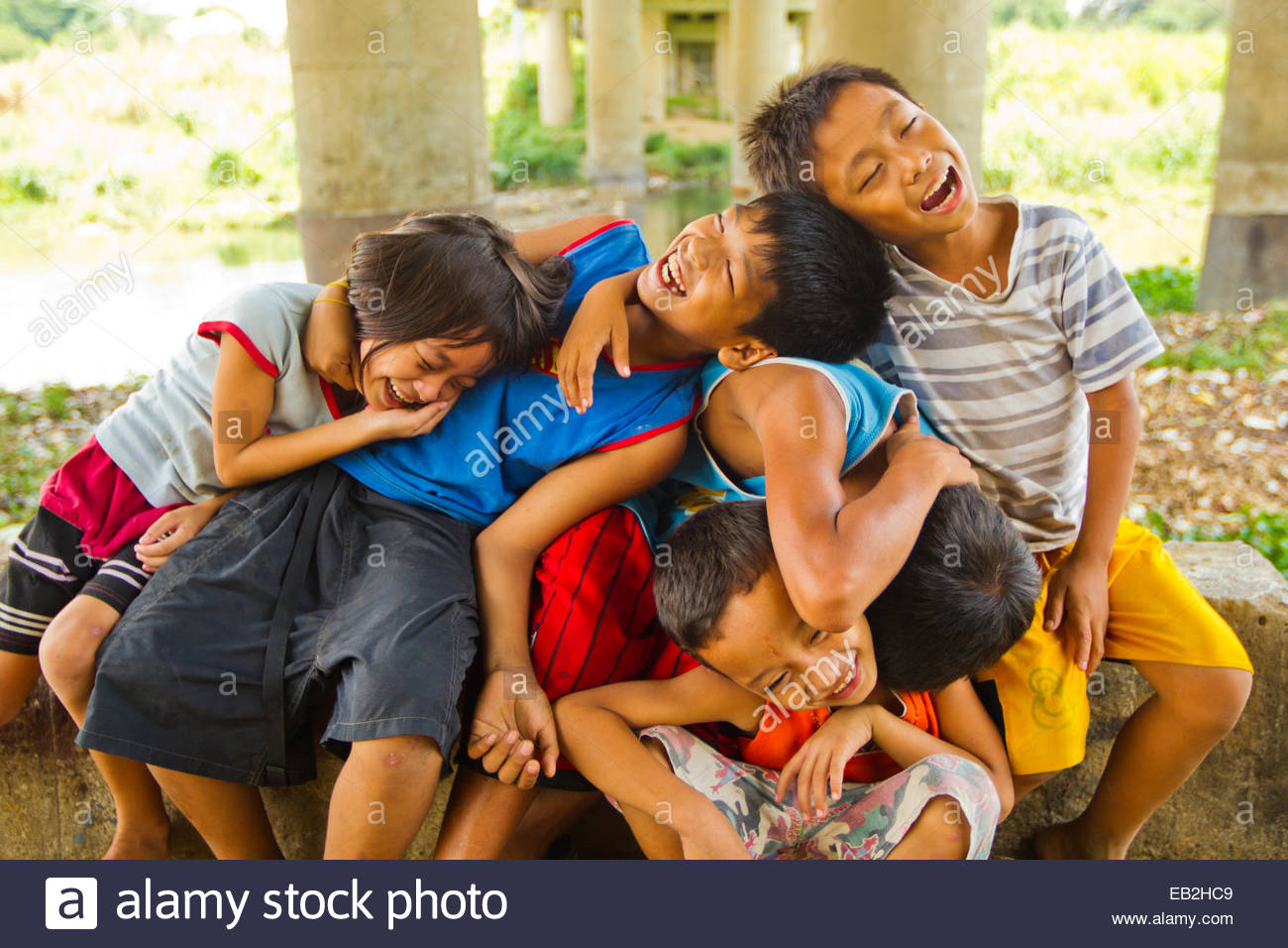 A group of kids that live under a bridge messing around and having fun. - Stock Image