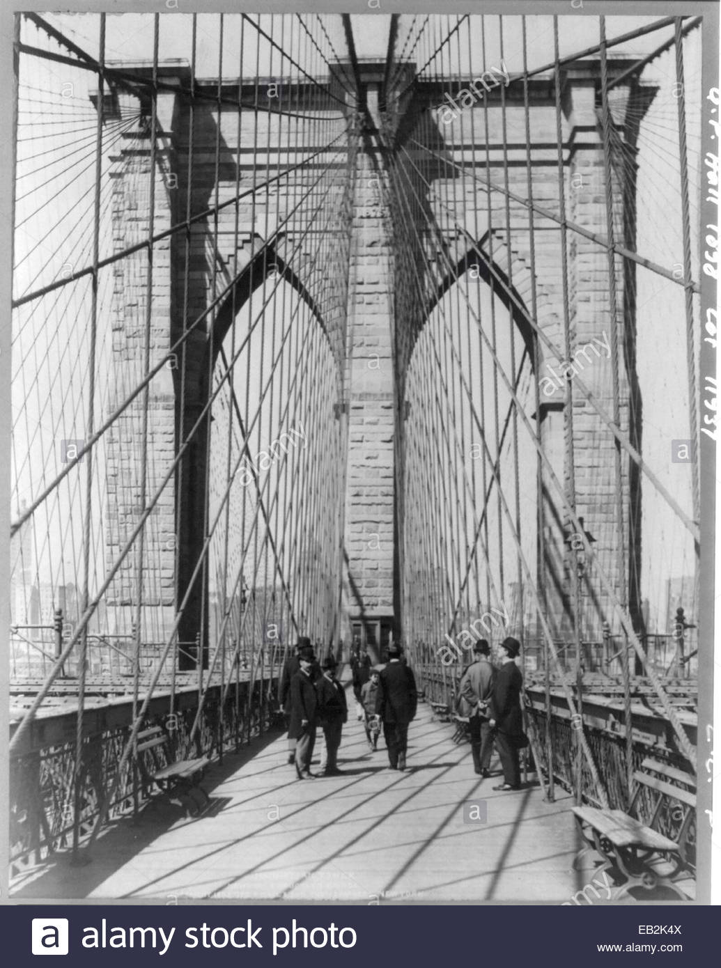 A photograph of people standing and walking on the Brooklyn Bridge promenade. - Stock Image