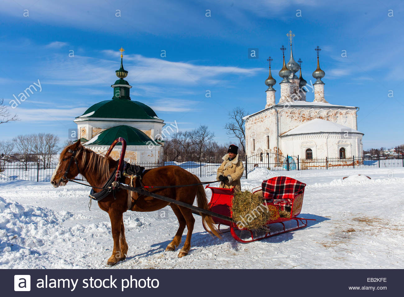 A person with a horse-drawn sleigh at one of the many traditional Russian Orthodox churches in the village of Suzdal, Stock Photo